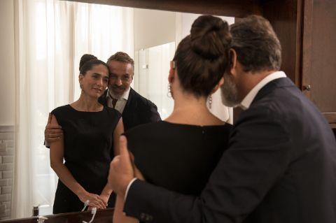 Пара со слуховым аппаратом за ухом смотрит в зеркало