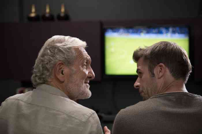 A Granpa whatches a football match on TV thanks to his invisible hearing aid