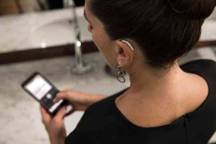 A girl with Behind-The-Ear hearing aid looking at her smartphone