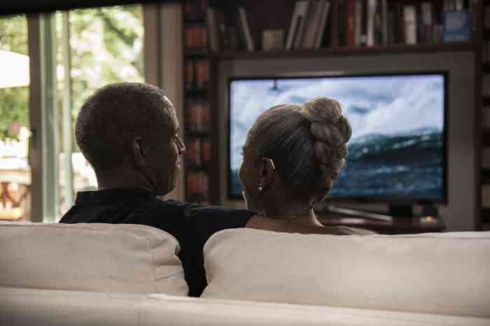 A couple wearing hearing aids is watching TV on the sofa