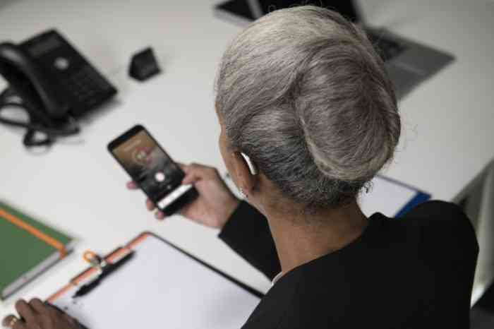 A business woman checks her hearing aid's app via smartphone