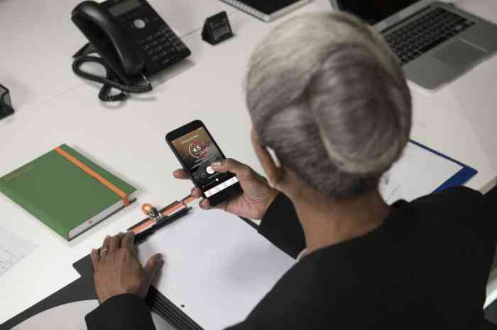 A woman upgrades her digital hearing aid via smartphone