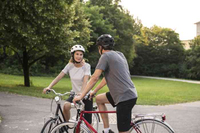 Couple with helmets talking outside on their bikes