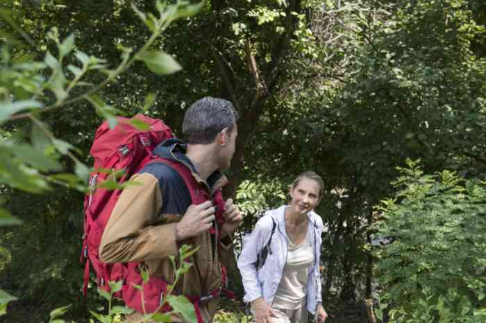 A man wearing his hearing aid and a woman walking through the trees