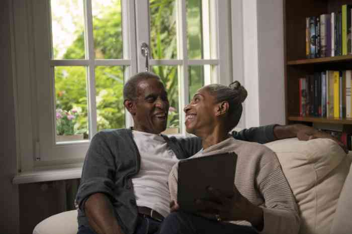 A couple with a tablet smiling on their sofa