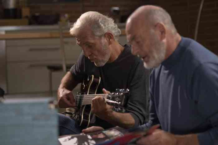 Two senior men singing and playing guitar