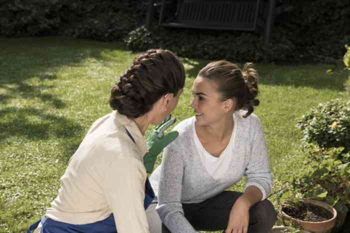 Two friends wearing hearing aids talking to each other gardening