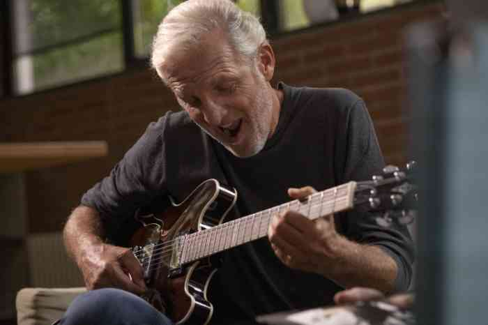 A senior playing guitar