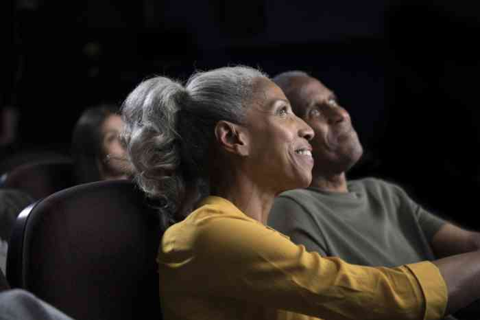 A woman wearing hearing aids enjoying a film at the cinema