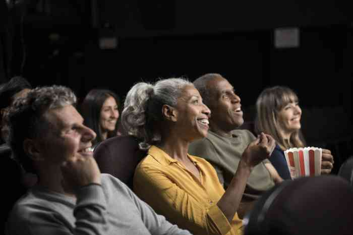 A woman laughs watching a movie at the cinema wearing her hearing aid