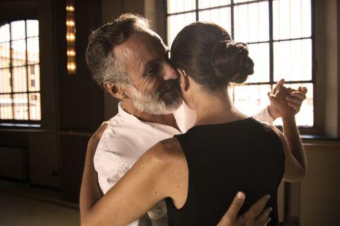 Пара танцует танго вместе, женщина в слуховых аппаратах