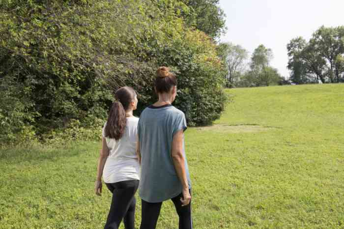 Two friends, wearing hearing aids, walking through the nature