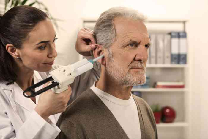 A senior man has his hearing checked by a hearing professional