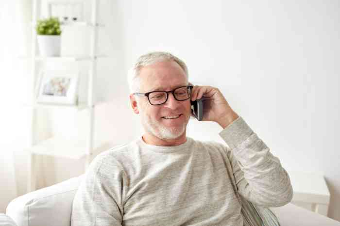 A smiley man is talking on a cordless phone