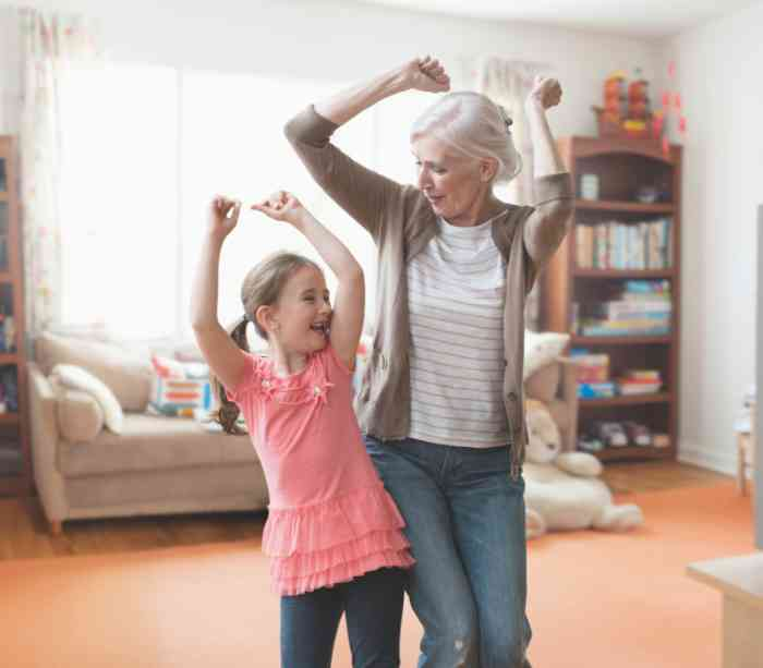 A Grandma wearing discreet hearing aids and her nephew dancing together