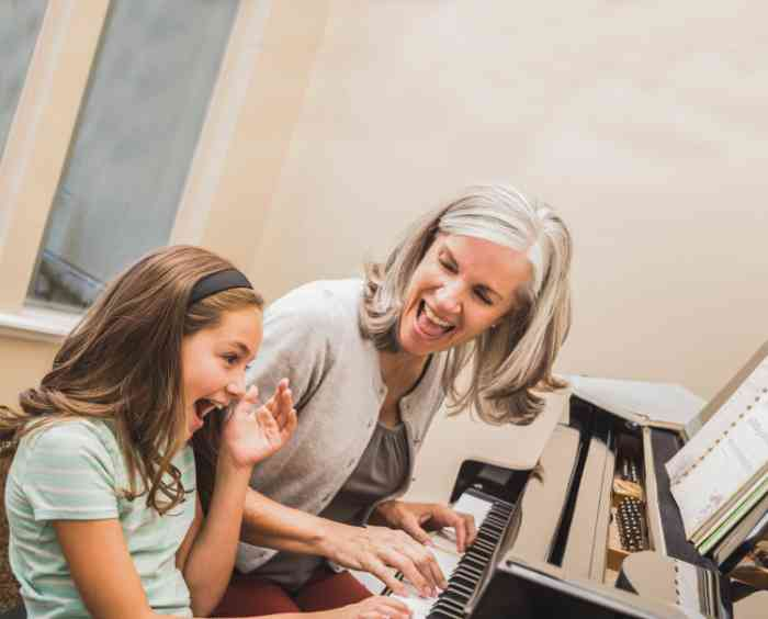 Grandmother and granddaughter laughing and playing the piano