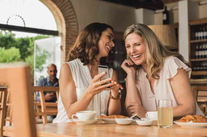 Two women laughing looking at their smartphone