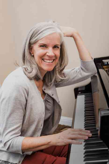 A woman is smiling next to a piano