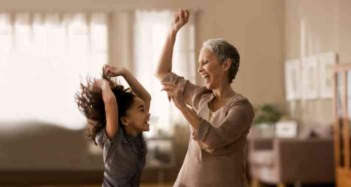 Grandmother and granddaughter laughing and dancing