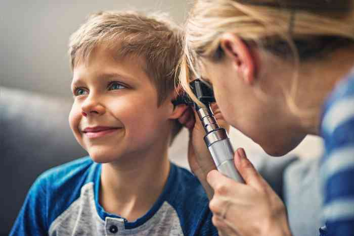 A kid is attending a hearing test with an expert audiologist