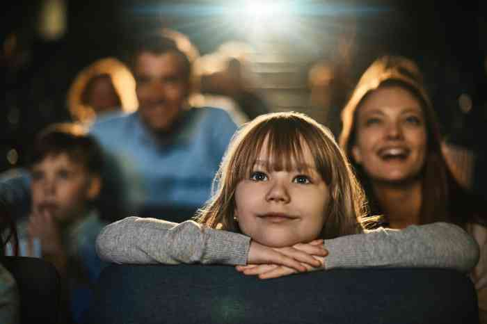 A young girl watching a movie at the cinema