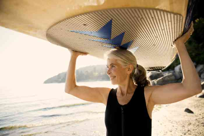 A woman is going surfing wearing her hearing aid