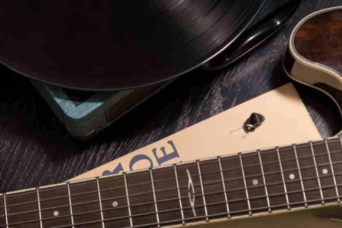 An in-the-ear hearing aid, a guitar and a vinyl